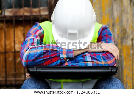 Bored construction Worker is lying on a laptop.Construction worker with white crash helmet is lying on a laptop. Royalty-Free Stock Photo #1724085331