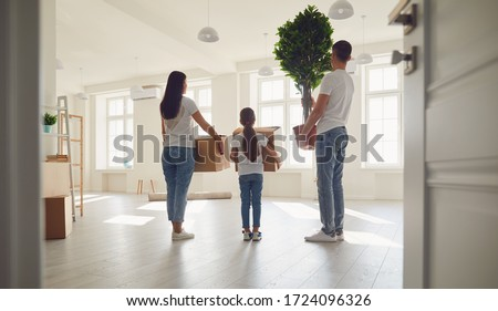 Happy family with children moving with boxes in a new apartment house. Back view. #1724096326