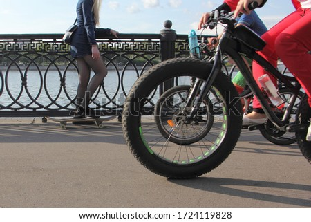 Fat bike wheel on background of skateboarder girl, summer outdoor activity sports, bicycle and skate board in Moscow Park #1724119828
