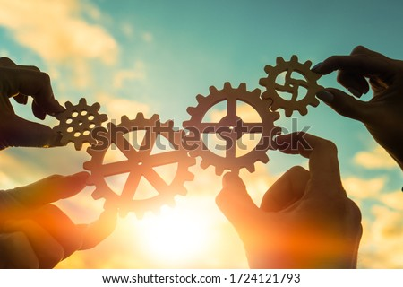 Four hands of businessmen connect gears to a puzzle on a background of sunset. Business concept idea, partnership, cooperation, teamwork, community, creative Royalty-Free Stock Photo #1724121793