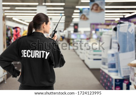 Security guard using portable radio transmitter in shopping mall, space for text Royalty-Free Stock Photo #1724123995