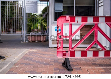 Red fence. Metal fence of the entrance to the park, building, office, university. The security booth is empty. No people. Ban on entry. Virus protection during an epidemic. Urban view. #1724149951