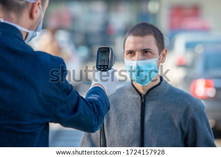 Temperature check at a supermarket of man, grocery store with thermal imaging camera. Image monitoring scanner to monitor the body temp of visitor customer #1724157928