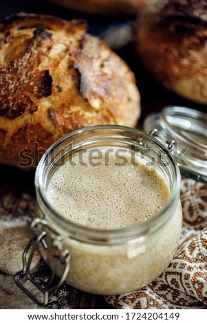 A jar with active rye sourdough for baking bread on a wooden table, close up #1724204149