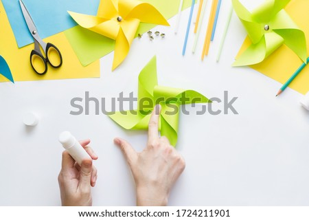 How to make paper green windmill toy with children at home. Step by step instructions. Hands making DIY summer project. Top view. Step 8. Glue remaining corners, overlaying each other #1724211901