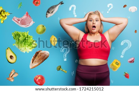 Fat girl in fitness suite wants to start a diet but has doubts about the food to buy. Cyan background #1724215012