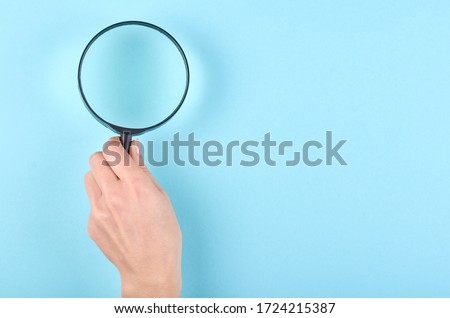 Hand with black magnifying glass on blue background. Flat lay, overhead view image. Copy space, template. Royalty-Free Stock Photo #1724215387