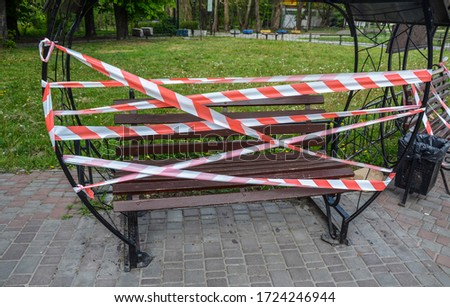 Bench fenced with red-white barrier tape. The access is denied during coronavirus COVID-19 pandemic. Quarantine period concept #1724246944