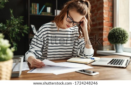 Pensive diligent female freelancer in glasses and casual clothes analyzing information in documents while sitting at table with graphics and notepad and using laptop in cozy contemporary apartment  #1724248246