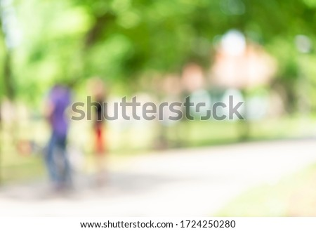 Defocused background of summer park with  people passing by