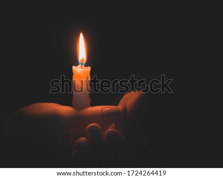 Burning candle in male hand on a black background.  #1724264419