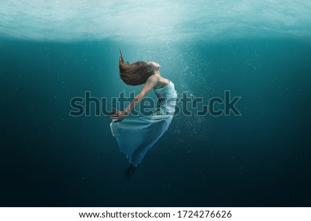 Elegant girl dancer in white dress in a state of levitation under the deep waters of the ocean with sunlight beaming on her face.  #1724276626