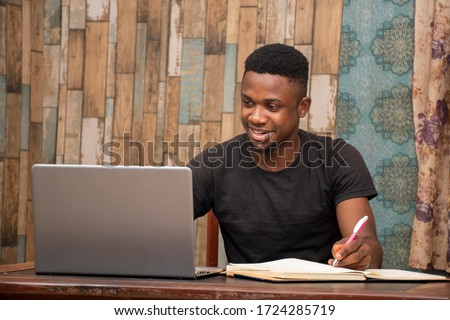 young african man studying at home using his laptop, receiving lectures online and taking notes, smiling #1724285719