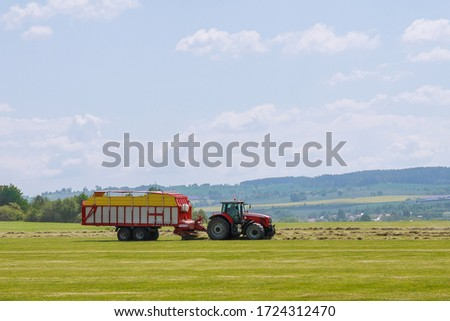 A red tractor rakes dry grass and places hay for loading and hauling. #1724312470