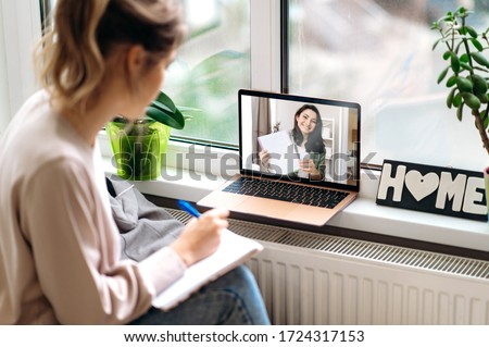 Online education. Young attractive girl is engaged in an individual lesson with a teacher on video communication using a laptop. Distant learning #1724317153