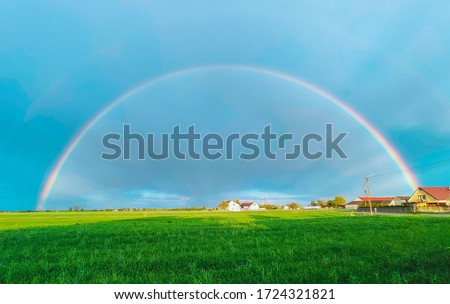 Summer rainbow landscape. Houses and field in the countryside in the background. Royalty-Free Stock Photo #1724321821