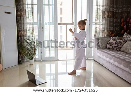 Taekwondo girl in kimono with white belt exercising at home in living room. Online education during coronavirus covid-19 lockdown, self isolation and social distancing concept #1724331625