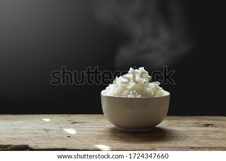 Hot Jasmine rice with steam on wooden table on dark background.  Soft Focus, Rustic tone picture.