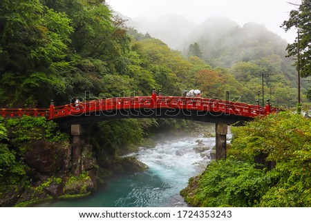People with umbrellas over red bridge Shinkyo crossing Daiya river. Rainy day, magical and mysterious atmosphere. Beginning of autumn, moth of October. Nikko, Japan, Asia. Horizontal picture