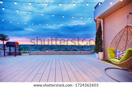 rooftop deck patio area with hanging chair on a sunset #1724362603
