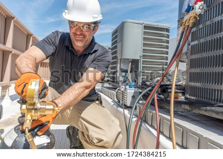 Hvac tech working on installing a new air conditioner unit on a roof top. Royalty-Free Stock Photo #1724384215