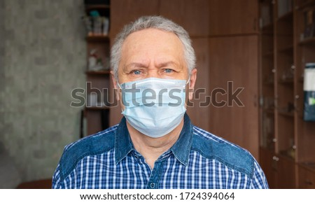 A man in a medical mask at home. He looks suspicious. #1724394064