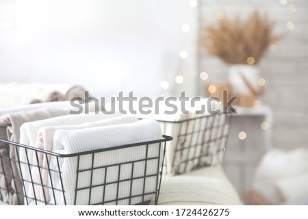 Close-up of white clothes and linen neatly folded in mesh metal containers in bedroom on background of blurred bed. Concept of the perfect organization. Advertising space Royalty-Free Stock Photo #1724426275