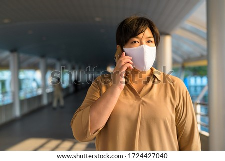 Overweight Asian woman with mask talking on the phone in the city #1724427040