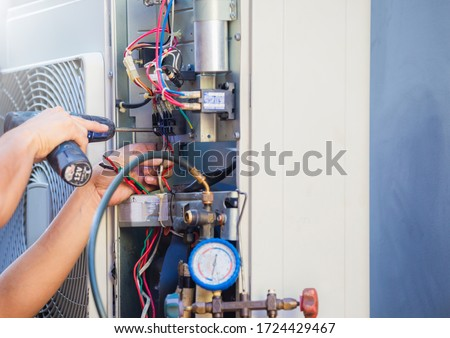 Male technician hands using a screwdriver fixing modern air conditioner, repairing and servicing, Maintenance and repairing concept #1724429467