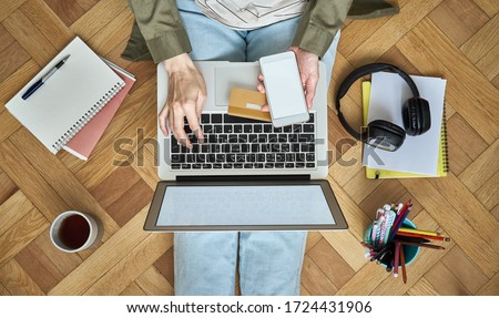 Online shopping concept. Unrecognizable woman sitting at floor, drinking tea and looking at laptop, pay for purchases by credit card #1724431906