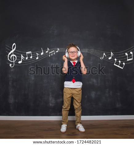 Child boy listening the music in headphones. School lesson