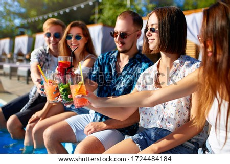 Group of friends having fun at poolside party clinking glasses with fresh cocktails sitting by swimming pool on sunny summer day. People toast drinking beverages at luxury villa on tropical vacation. #1724484184