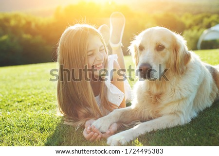 A child with a dog in nature. girl playing with a dog on green grass at sunset time. Royalty-Free Stock Photo #1724495383