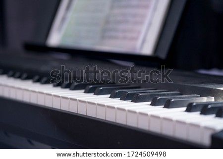 closeup side view of piano keyboard with low light Royalty-Free Stock Photo #1724509498