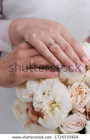 The hands of the newlyweds. The hands of the bride and groom against the background of a bouquet. Wedding rings in the hands.  #1724510404