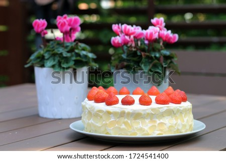 Fresh and delicious homemade summertime theme strawberry, almond and cream cake. Topped with whipped cream, fresh berries and almond slices. Cheerful cake for celebrations like bday or Mother-s day.