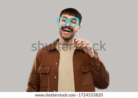 party props, photo booth and people concept - happy smiling young man with paper glasses over grey background