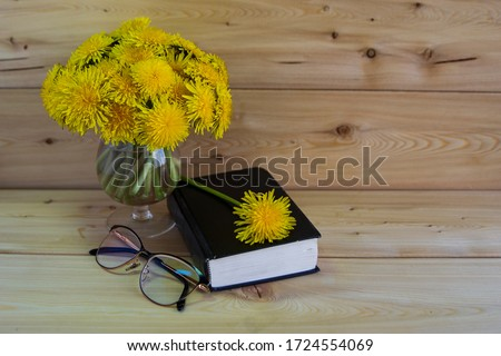 A Bible, glasses, a bunch of yellow dandelions on a wooden background. Warm tone. There is a place for the inscription. Good morning.