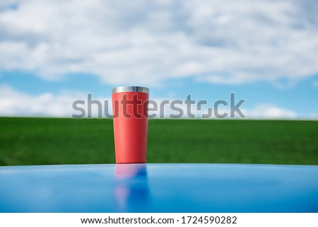 Close-up picture of red thermos cup with tea, standing on blue car top in front of green field and light blue sky with white clouds Picnic in countryside. Nature protection concept.