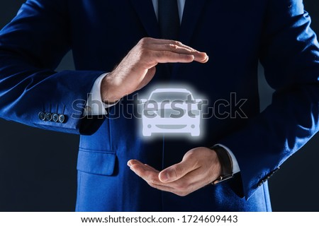 Man demonstrating image of auto on dark background, closeup. Car insurance