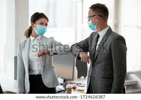 Businessman and businesswoman with medical mask in office. Greetings in Covid-19 time. Royalty-Free Stock Photo #1724626387