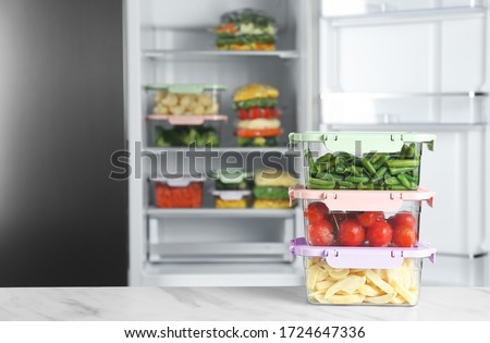 Containers with different frozen vegetables on white marble table near open refrigerator #1724647336