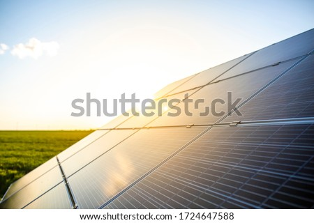 Solar power cells, close up on photovoltaic solar panels with green field in the back. Royalty-Free Stock Photo #1724647588