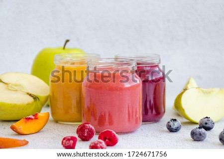 Baby food. Homemade fruit puree. Variety of apple puree or applesauce with frozen peach, raspberries and blueberries in three glass jars on a light background. Healthy food. Horizontal, copy space Royalty-Free Stock Photo #1724671756