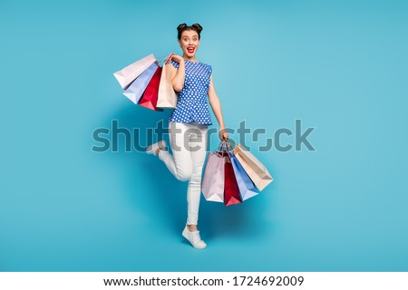 Full length photo of pretty lady carry many packs spree addicted shopaholic rejoicing shopping center wear dotted blouse white pants footwear isolated blue color background #1724692009