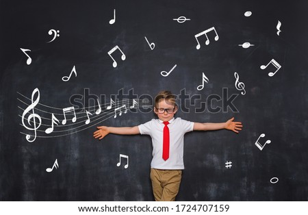 Music in child's life. Note in kid's head. Happy boy with raised hands and draw music notes on chalkboard