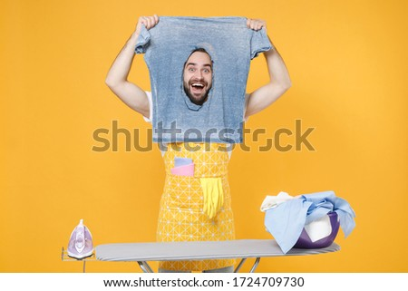 Excited young man househusband in apron ironing clean clothes on board while doing housework isolated on yellow wall background studio. Housekeeping concept. Mock up copy space. Hold burnt t-shirt