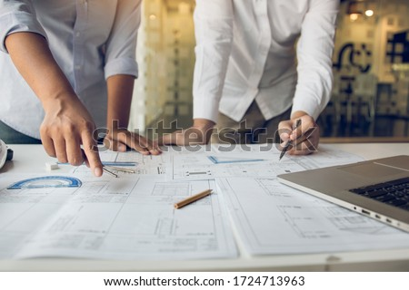 Engineers are helping to design work on blueprints and collaborate on structural analyzing of project types. Royalty-Free Stock Photo #1724713963