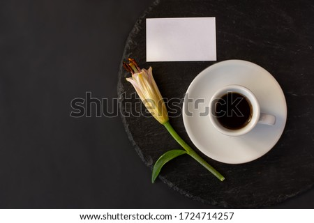 Cup of black coffee and fresh spring bud of lily flower with clean white business card without massage on a round slate on a black background. Romantic stylish breakfast. Date on restaurant