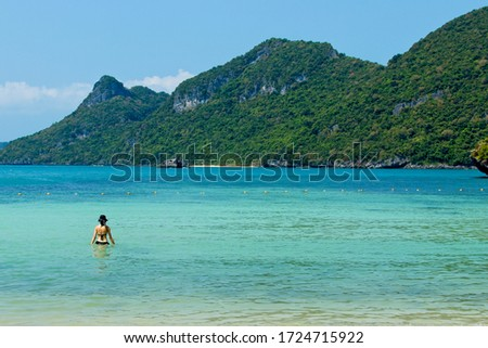 An unrecognizable woman swimming in the sea in the Ang Thong Marine National Park near Koh Samui in Thailand.  Tourism background image.